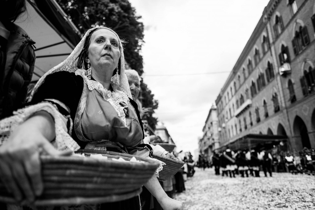 Donne in costume tradizionale attendono il passaggio del Santo con ceste piene di fiori